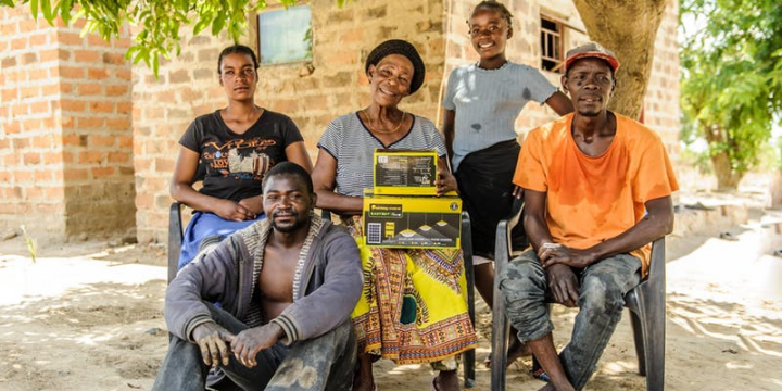 A Zambian family pose with their newly purchased solar home system.