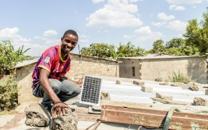ReadyPay customer Steven Miyoba shows the solar panel on his roof, on the outskirts of Lusaka, Zambia